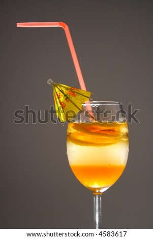Triple layered drink with spiral lemon slice in studio light - stock photo