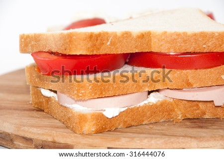 Triple sandwich with salami tomato and sour cream.