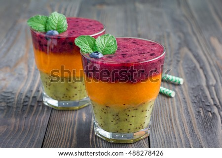 Triple smoothie in glass: kiwi-mint, mandarin-apricot and strawberry-blueberry, horizontal, copy space