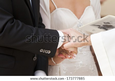 Tris hands between husband and wife priest during the celebration of marriage