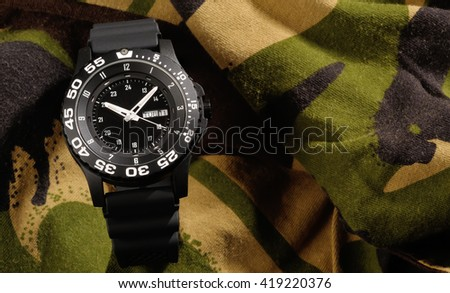Tritium military watch on camouflage clothing - stock photo