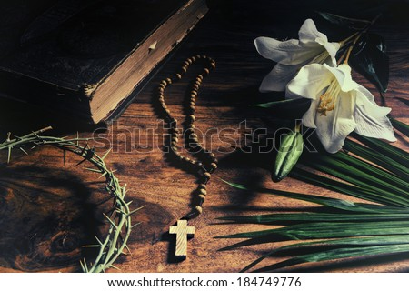 Triumph, Passion, Crucifixion and Resurrection concept.  Iconic symbols relating to Palm Sunday and Easter rest upon a rustic table - Bible, palm branch, crown of thorns, cross, and white lily.      - stock photo