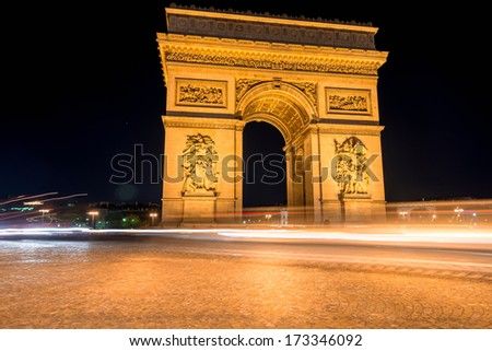 Triumphal arc in Paris at night with car trails - stock photo