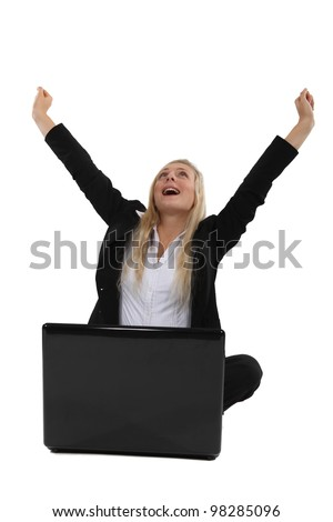 Triumphant businesswoman sitting at a laptop - stock photo