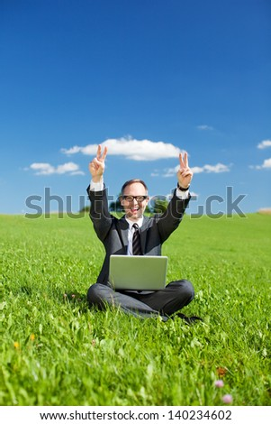 Triumphant man giving a victory sign and laughing with his hands in the air as he sits in the middle of a green grassy field with his laptop balanced on his knees - stock photo