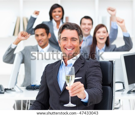 Triumphant manager and his team drinking champagne in the office - stock photo