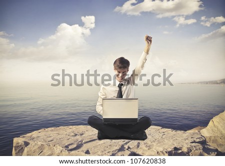 Triumphing young businessman in front of a laptop with seascape in the background