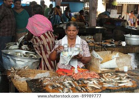 TRIVANDRUM - DEC 02: Unidentified woman sells fish in a crowded market on December 02, 2011 in Chalai,Trivandrum, India. Chalai is the biggest market in the capital city of Kerala state.