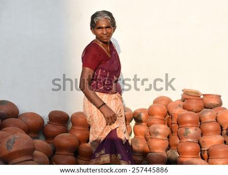 TRIVANDRUM, KERALA, INDIA, MARCH 03, 2015: Woman Entrepreneur. Woman empowerment. Woman power. Bread winner. A proud lady sells pots during Attukal ponkala festival in the Thiruvananthapuram city. - stock photo