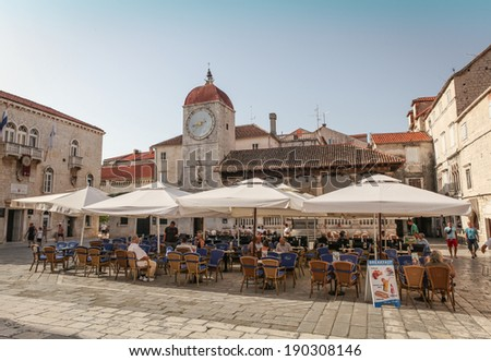 TROGIR, CROATIA - AUGUST 6, 2012: Main town square in historic center of Trogir with San Sebastian church clock tower and people sitting in a restaurant. Trogir is a historic town in Croatia - stock photo