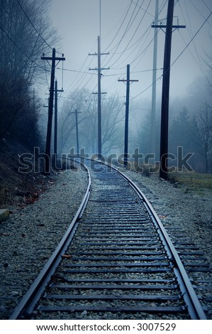 trolley track in the misty morning with telephone poles