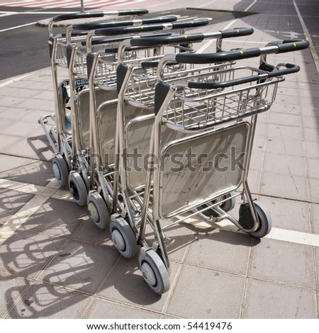 Trolleys in front of airport terminal - stock photo