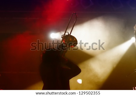 Trombone player silhouette on stage and abstract light