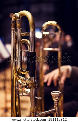 Trombones in the hands of musicians on stage - stock photo