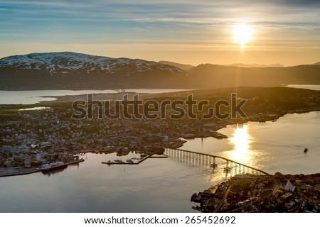 Tromso city in Tromsoya Island as seen from Mount Storsteinen under the Midnight Sun in Norway. - stock photo