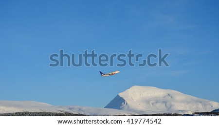 TROMSOE, NORWAY - MARCH 16, 2014: SAS airplane climbing after takeoff from Tromsoe airport Langnes. SAS is the flag carrier of Sweden, Norway and Denmark, and the largest airline in Scandinavia.