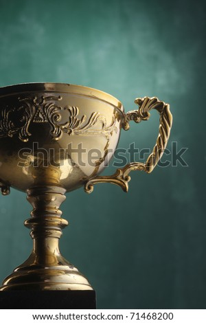 Trophy cup isolated on the green background. - stock photo