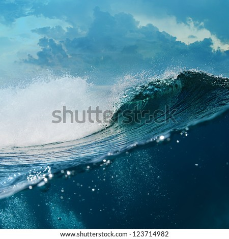Tropical background design template. Cloudy Seaview Big Breaking surfing ocean wave in daylight with underwater part - stock photo
