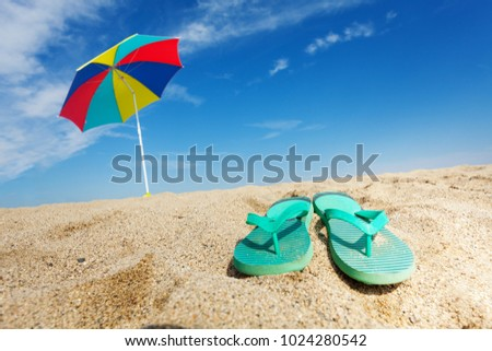 Tropical background with flip flops and umbrella