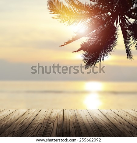 Tropical background with wooden empty table, coconut palm tree and beautiful beach at sunset - stock photo
