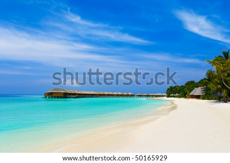 Tropical beach and bungalows - travel vacation background - stock photo