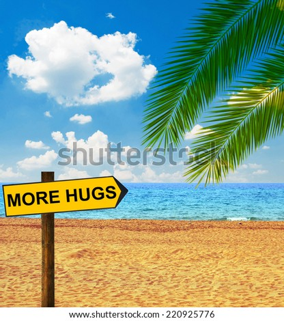 Tropical beach and direction board saying MORE HUGS - stock photo
