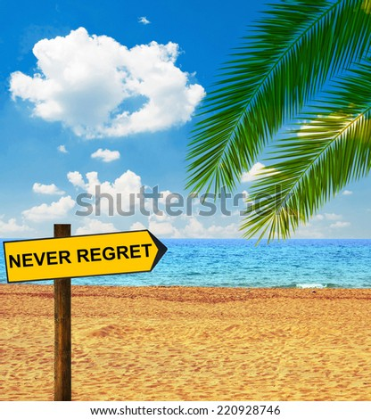 Tropical beach and direction board saying NEVER REGRET - stock photo