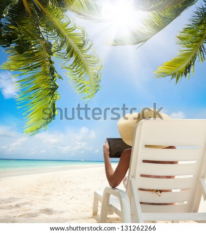 Tropical beach and woman relaxing with tablet computer sitting on the sun chair - stock photo