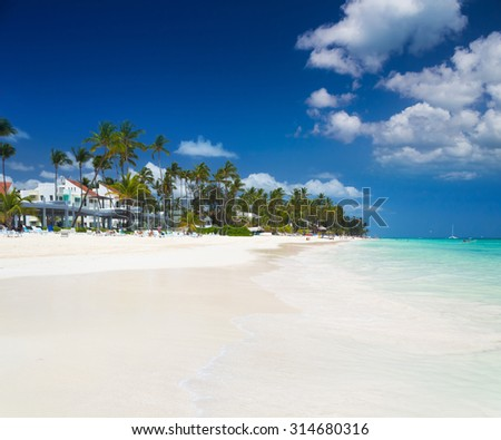 Tropical beach Bavaro with white sand, palm trees and perfect blue sky in Punta Cana - stock photo