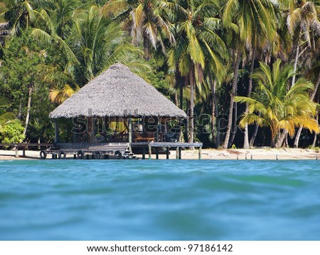 Tropical beach hut overwater with thatch palm roof viewed from water surface, Caribbean sea - stock photo