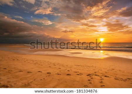Tropical beach in ebb time on sunset background - stock photo