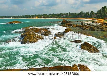 Tropical beach in Indian Ocean, Srilanka, rocks in the  water - stock photo