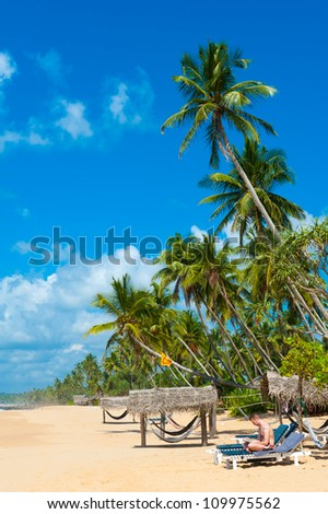 Tropical beach in Sri Lanka. Man reading book sitting on the desk chair.