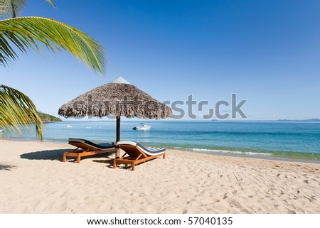 Tropical beach landscape with deckchair and parasol, from Nosy Be, Madagascar - stock photo
