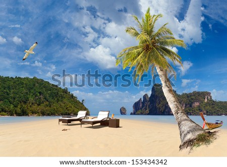 Tropical beach of Ko Phi Phi Don island with sunbeds and long tailed boat  - stock photo