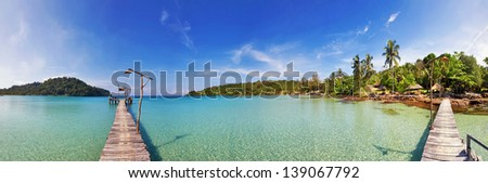 Tropical beach panorama with pier, palm trees on small island - stock photo
