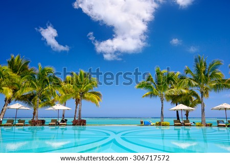 Tropical beach resort with  lounge chairs and umbrellas, Mauritius - stock photo