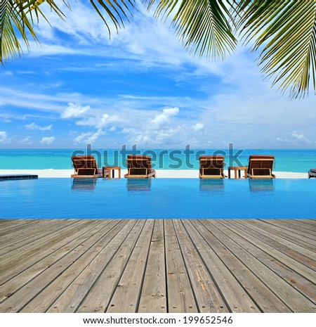 Tropical beach resorts swimming pool overlooking the sea -- Summer holidays concept - stock photo