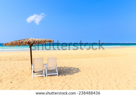 Tropical beach scenery with parasol and deck chairs in Boavista, Cape Verde - Cabo Verde - stock photo