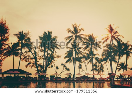 Tropical beach view. Palm trees, rest area with sun umbrellas. Vintage instagram effect. - stock photo