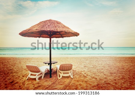 Tropical beach view. Two beach chairs with sun umbrellas. Vacation concept. - stock photo