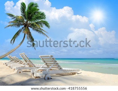 Tropical beach with a sun-lounger facing the blue sea - stock photo
