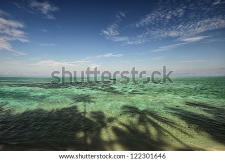 tropical beach with blue sky and the shadows from the trees - stock photo