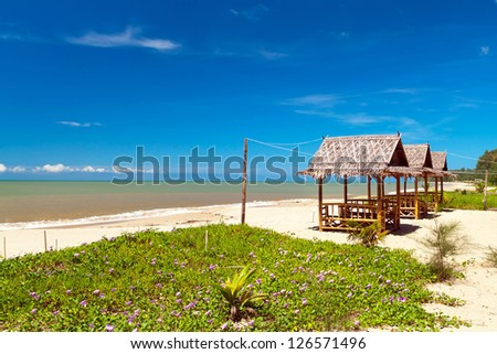 Tropical beach with bungalows in Thailand - stock photo