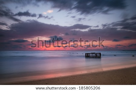 Tropical Beach with Empty Cage in the Sea at Colorful Sunset