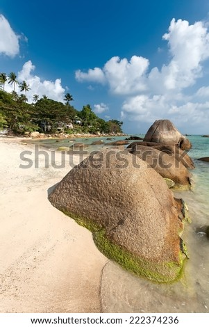 Tropical beach with granite boulders on sand and turquoise water. - stock photo