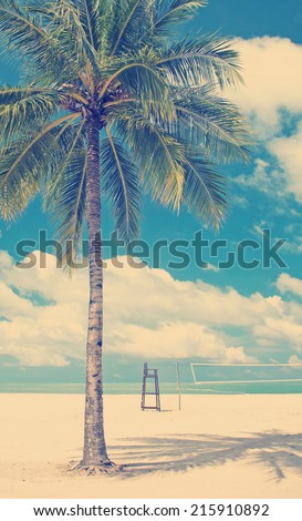 Tropical beach with palm tree, clean sand and volleyball court with Instagram style filter - stock photo
