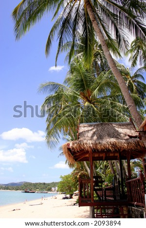 Tropical beach with palm trees and thatched beach hut - stock photo