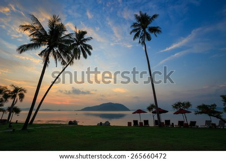 Tropical beach with palm trees at sunset time and reflections on water surface. - stock photo