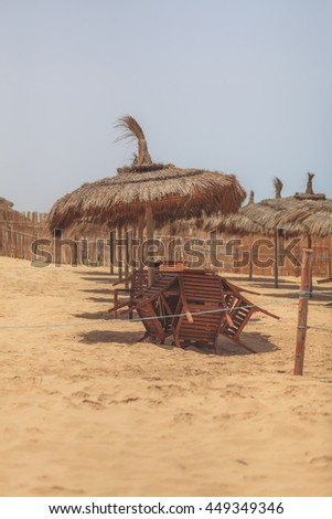 Tropical beach with straw umbrellas and some white sunbeds - stock photo